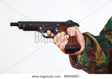 Hand in camouflage uniform with discharged army gun on white background