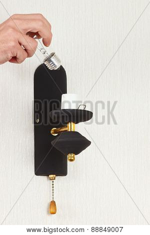 Hand unscrews incandescent bulb in luminaire on white wall