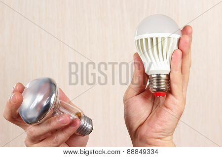 Hands compared incandescent bulb and ecofriendly led lamp on light wood background