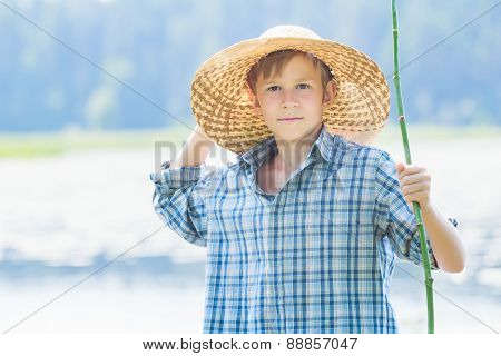 Portrait of teenager with twig fishing rod and hand behind his head