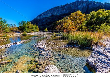 Blue Skies and Bright Beautiful Fall Foliage On The Crystal Clear Rocky Frio River in Texas