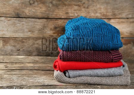 Knitting clothes on wooden background
