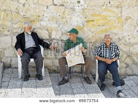 OLD CITY, JERUSALEM-JUNE 9: Three senior men sit on the steps of Casa Nova Road. Christian Quarter, Old City, Jerusalem, relaxing & enjoying a conversation about events in the newspaper, June 9, 2007.
