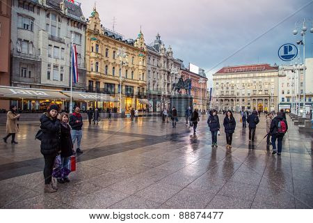 ZAGREB, CROATIA - 11 MARCH 2015: Zagreb's main square with Ban Josip Jelacic statue and surrounding buildings on a wet evening.