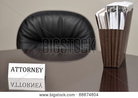 Attorney business card on desk with files and chair