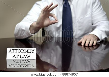 Attorney at Law sitting at desk with OK sign for good job or done deal