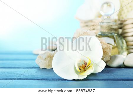 Still life with beautiful blooming orchid flower, spa treatment on wooden table, on bright background