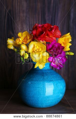 Colorful freesia in vase on wooden background