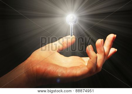 Female hand with key on dark background