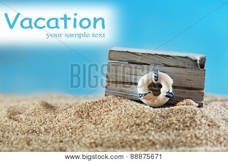 Wooden box with lifebuoy on sand on blue background