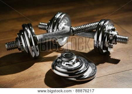 Dumbbells on wooden floor, on dark background