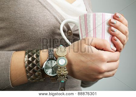 Stylish bracelets and clock on female hand on bright background