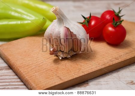 Single Garlic Bud On Chopping Board With Tomatoes