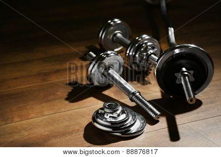 Dumbbells on wooden floor, on dark background