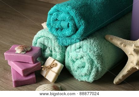 Spa composition with towels and soap on wooden background