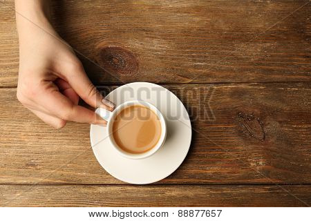 Female hand holding cup of coffee on wooden background