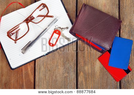 Open notebook, pen, key, glasses and wallet on wooden table background