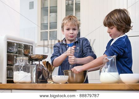 Two boys whisking dough for pastry in a stainless steel in a kitchen