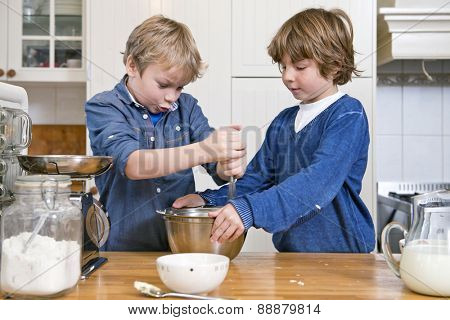 Boys mixing dough in a bowl using a whisk during a baking workshop for kids at a birthday party