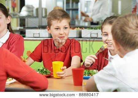 Group Of Pupils Sitting At Table In School Cafeteria Eating Meal