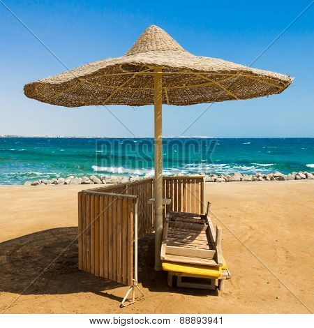 Deserted beach with wattled sun umbrellas.