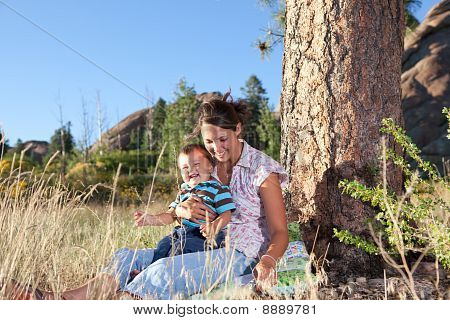 Mother And Son Under A Big Pine Tree