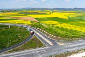 foto of rape-seed  - Aerial view of road passing through a rural landscape with blooming rape in northern Greece  - JPG