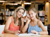 picture of mums  - A teenage girl with headphones sitting in a library with her mum - JPG