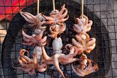 stock photo of squid  - Traditional Thai Squid Barbecue on the street along the beach - JPG