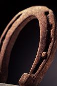 pic of shoes colorful  - Color shot of a rusty horse shoe on a dark background - JPG