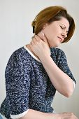 image of neck brace  - Adult woman with neck pain on a light background - JPG