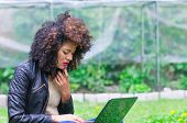 foto of saddening  - exotic beautiful young worried girl with dark curly hair using laptop in the garden - JPG