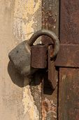 stock photo of lock  - Old locked rusty lock on a steel door - JPG