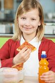 image of school lunch  - Girl Sitting At Table In School Cafeteria Eating Unhealthy Packed Lunch - JPG