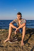 picture of nearly nude  - Attractive young fashion sexy man sitting on a rock near the sea water with shoes beside him - JPG