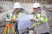 picture of engineering construction  - Civil Engineer and Surveyor at at construction site are inspecting ongoing production according to design drawings - JPG