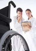 picture of rollator  - two women doctors are looking at the card of the patient and a wheelchair is in the frond - JPG