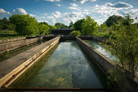 image of feces  - The slime covered sedimentation tanks or pools of an old abandoned water sewage treatment facility - JPG
