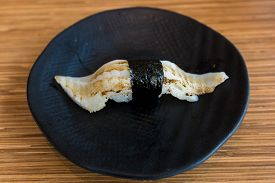 pic of halibut  - A piece of Halibut sushi on a black plate - JPG
