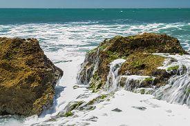 stock photo of slam  - Turquoise rolling wave slamming on the rocks of the coastline  - JPG