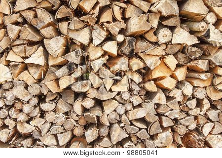Ready firewood. Various kinds of wooden logs stacked on top of each other.