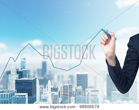 A Hand Is Drawing A Growing Line Graph On The Glass Screen. New York City Space On The Background.