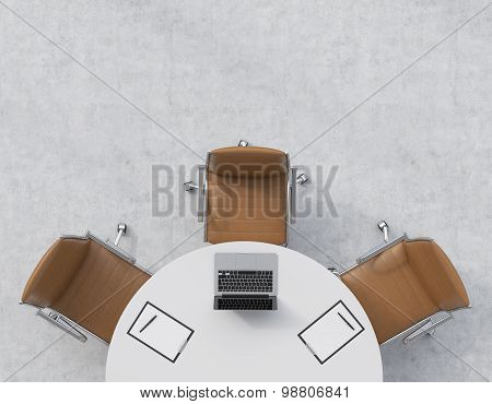 Top View Of A Half Of The Conference Room. A White Round Table, Three Brown Leather Chairs. A Laptop