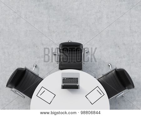 Top View Of A Half Of The Conference Room. A White Round Table, Three Black Leather Chairs. A Laptop