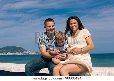 Happy Pregnant Couple And Child Boy On The Coast