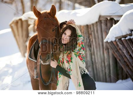 beautiful young woman in Russian national scarf with a horse in the countryside in winter