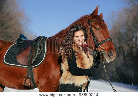 beautiful young woman and horse in winter forest