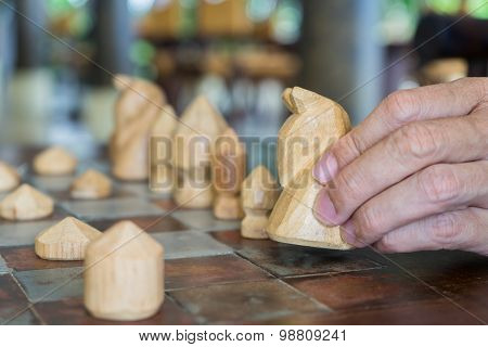Man's Hand Holding Wooden Chess To Check Match