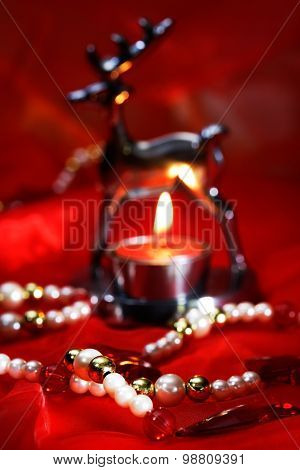 Christmas Decoration With Burning Tea Light And Beads On Red