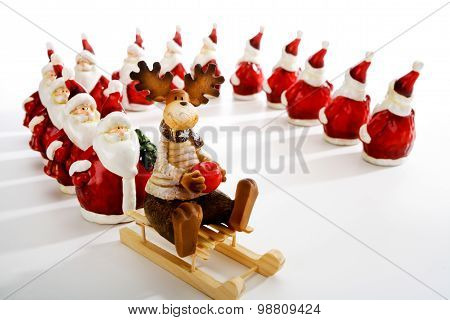 Santa Clauses Queuing At Sledge With Elk